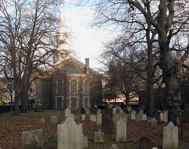 Looking east across graveyard at Flatbush Dutch Reformed Church on a mostly cloudy afternoon